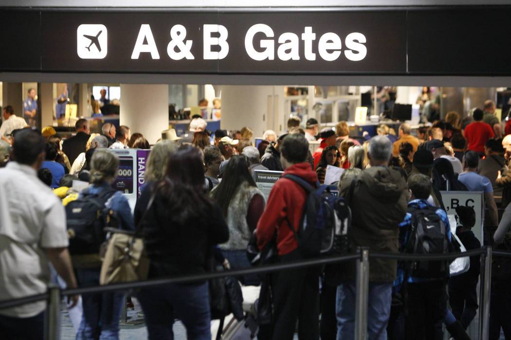 Passengers wait in line to go through security at McCarran International Airport Terminal 1 in ...