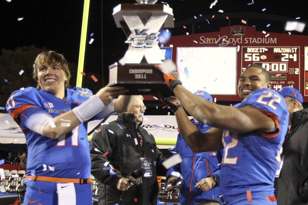 Boise State quarterback Kellen Moore, left, and running back Doug Martin hoist the trophy after ...
