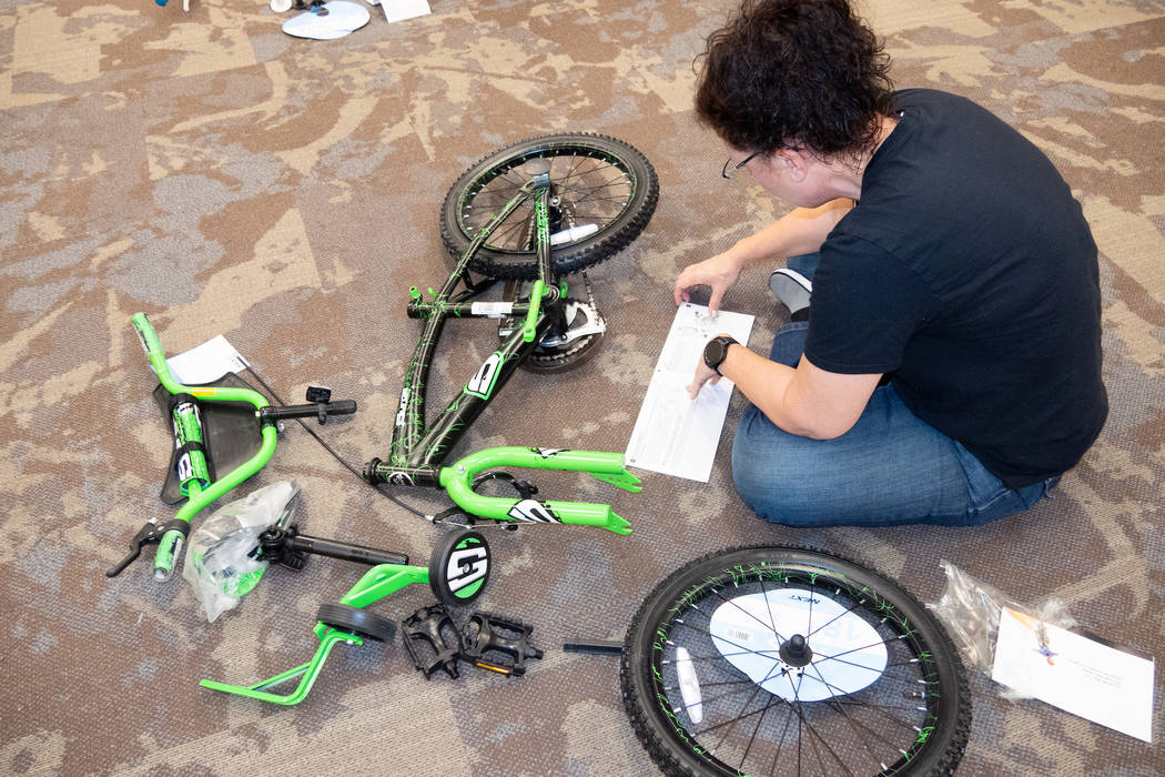 GLVAR member Diana Jenkins assembles a bike to be donated to the annual KLUC toy drive. (GLVAR)