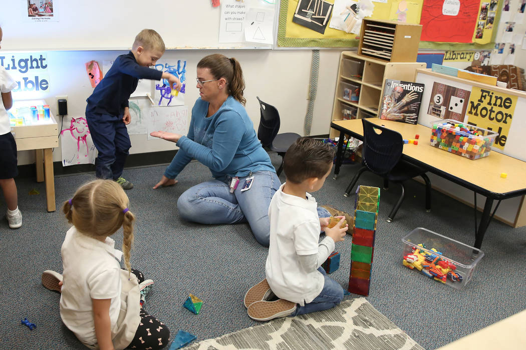 Specialized Programs Teaching Assistant, Heather Atkin, plays with pre-kindergarten students, i ...