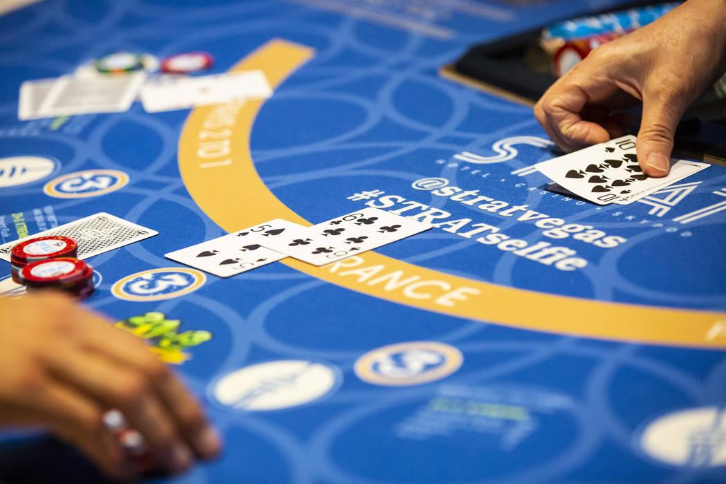 Blackjack dealer Amal Almisber, right, works the table at The Strat in Las Vegas on Wednesday, ...
