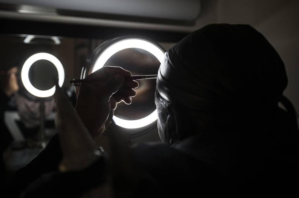"Raiders super fan Wayne Mabry, known as ""Violator,"" applies makeup in his hotel room ..."