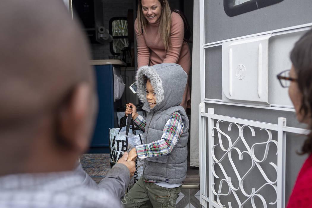 Jill Ajayi, back, and her son Olamide Ajayi, 6, center, surprises Olamide's mentor Lisa Bernaue ...