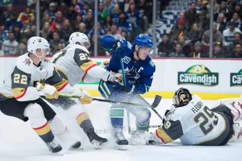 Vegas Golden Knights' Nick Holden (22) and Shea Theodore (27) stop Vancouver Canucks' Bo Horvat ...