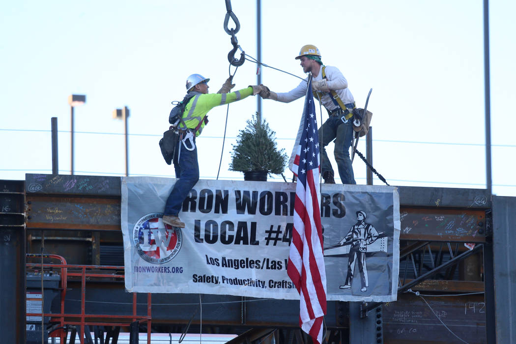 Workers shake hands after place during a topping-off ceremony for the Expo at World Market Cen ...