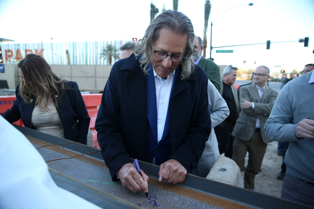 Bob Maricich, president and CEO of International Market Centers, signs a beam during a topping- ...