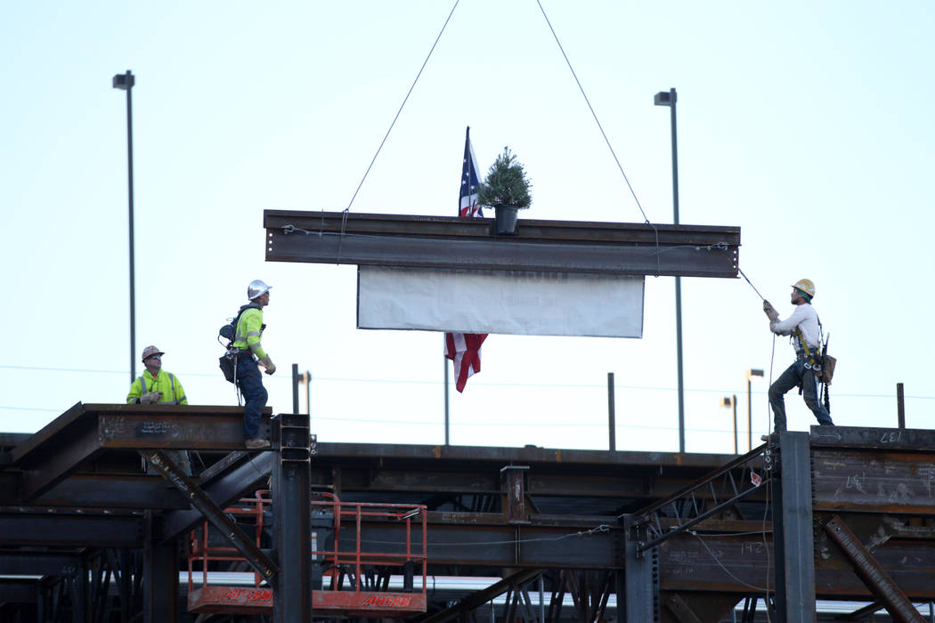 Workers move a beam into place during a topping-off ceremony for the Expo at World Market Cente ...
