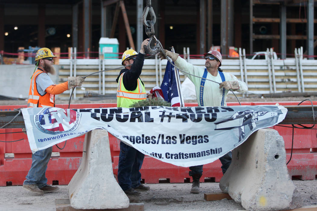 Workers secure a beam during a topping-off ceremony for the Expo at World Market Center in Las ...