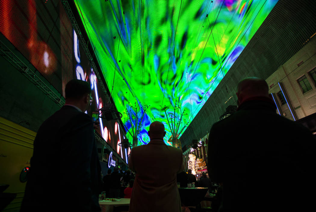 People watch the recently-upgraded Viva Vision screen during a preview of the new light show, & ...