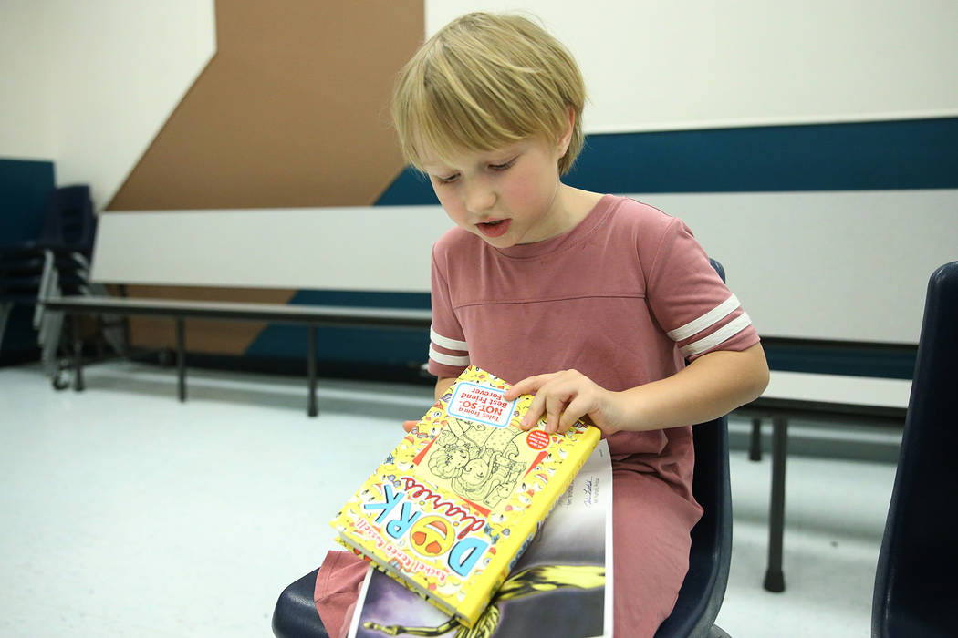 Second-grade-student Emily Krupka, 7, shows a book she got from a book vending machine at Frank ...