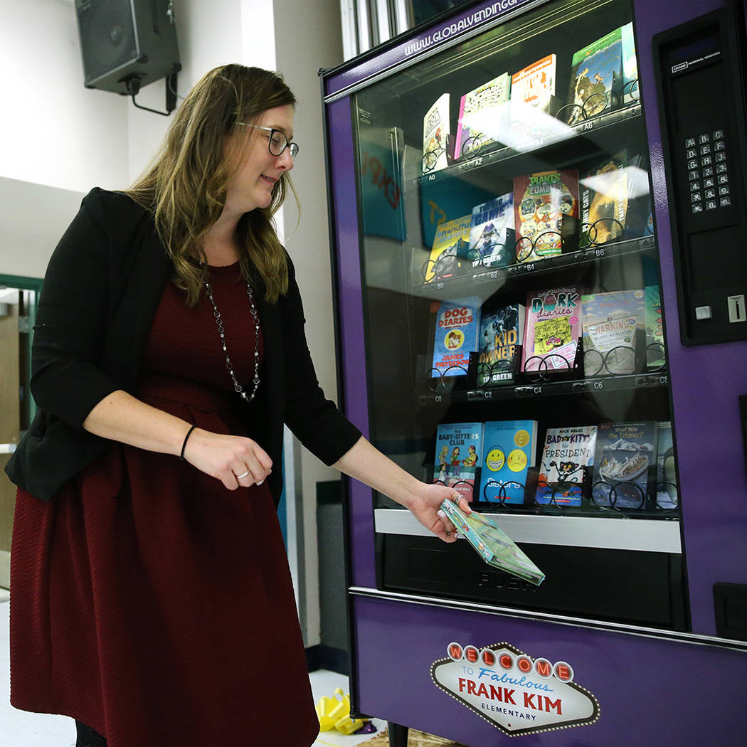 Assistance Principal Michelle Thom grabs a book from a book vending machine at Frank Kim Elemen ...