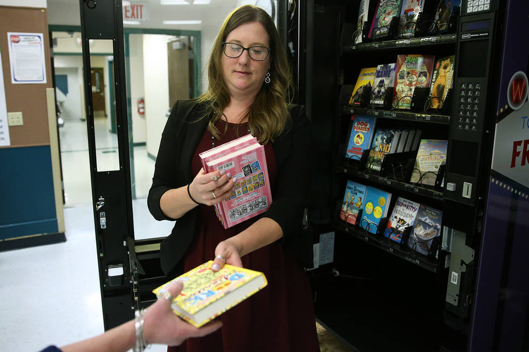 Assistance Principal Michelle Thom hands out a book from the book vending machine at Frank Kim ...