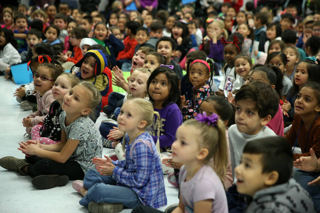 Students react as a book bending machine is unveiled during a ceremony at Frank Kim Elementary ...