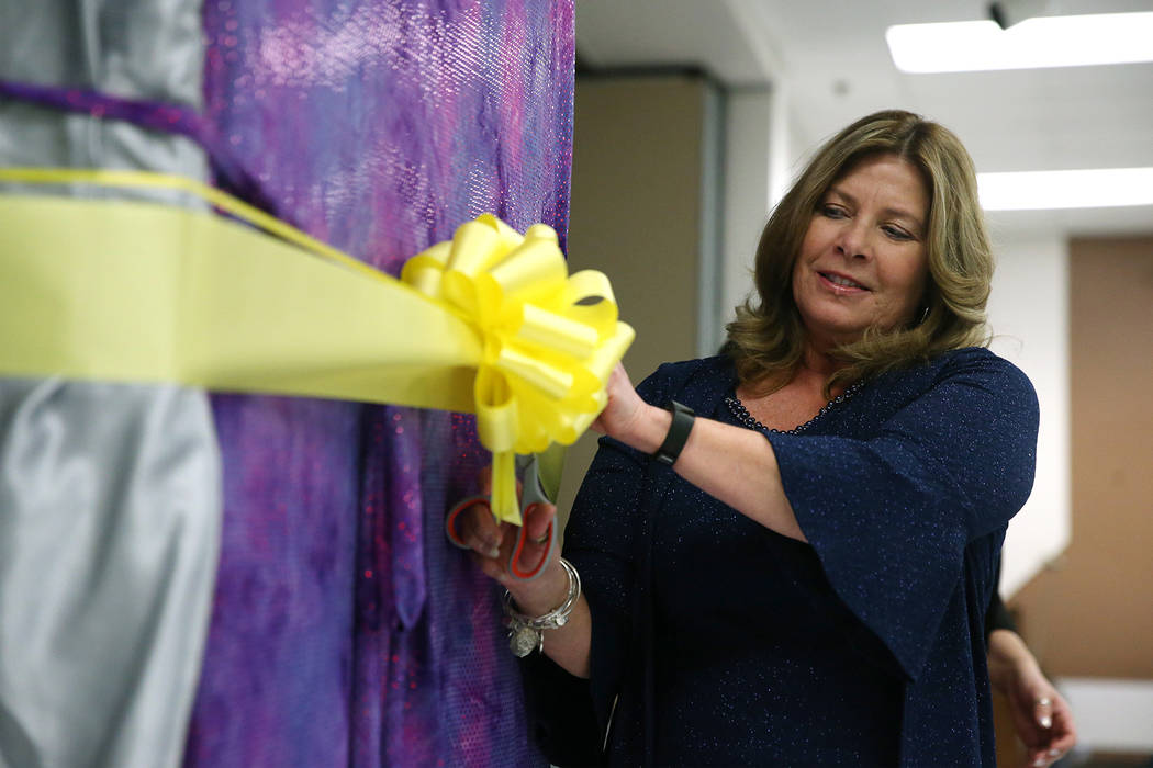 Principal Cathleen Furtado cuts a ribbon during an unveiling ceremony for a book bending machin ...