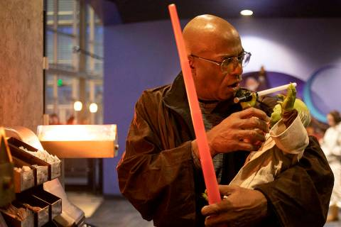 George R. Addison III pretends to feed his Yoda doll at the Star Wars: The Rise of Skywalker pr ...