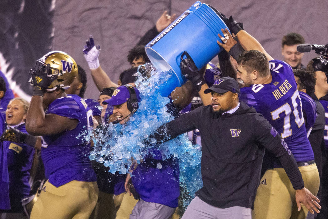 Washington Huskies head coach Chris Petersen, center, is soaked with Powerade and ice ending th ...