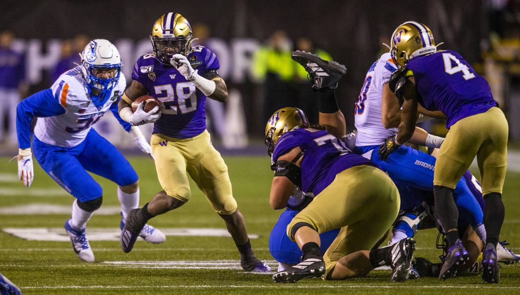 Washington Huskies running back Richard Newton (28, left) looks for open field as Boise State B ...
