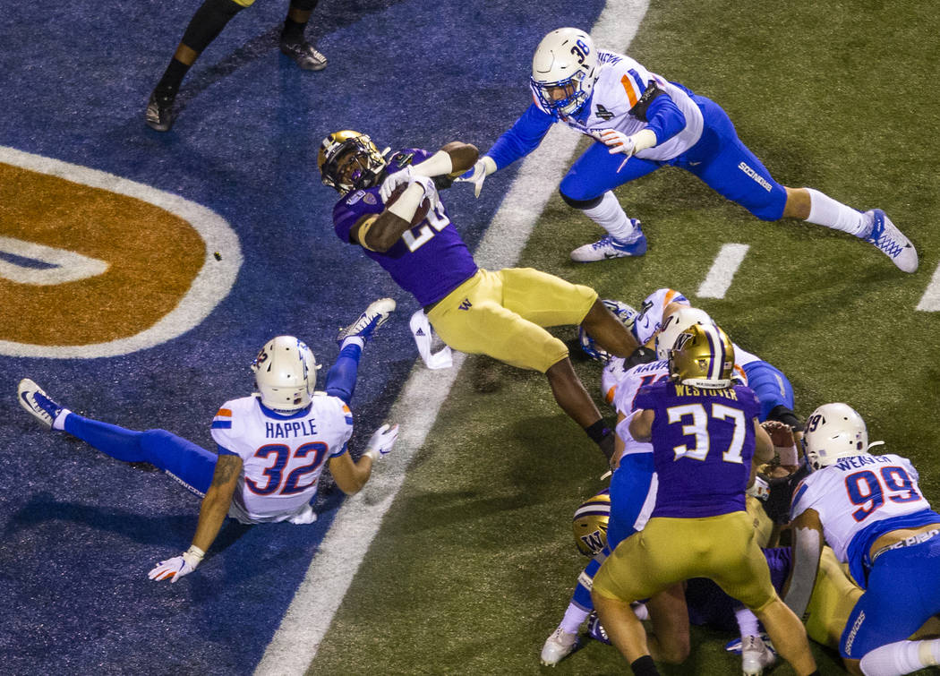 Washington Huskies running back Richard Newton (28, center) falls backwards into the end zone b ...
