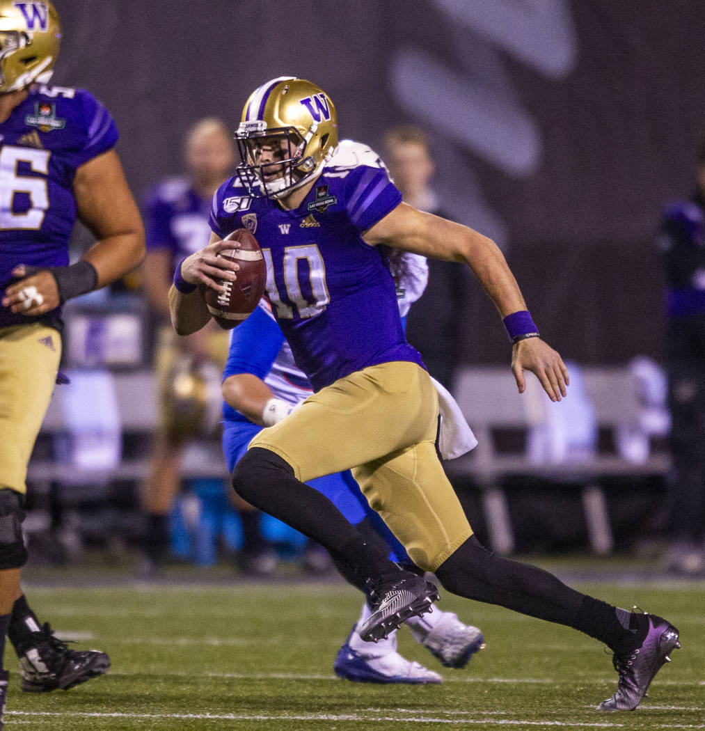 Washington Huskies quarterback Jacob Eason (10) looks for more yards on a run versus the Boise ...