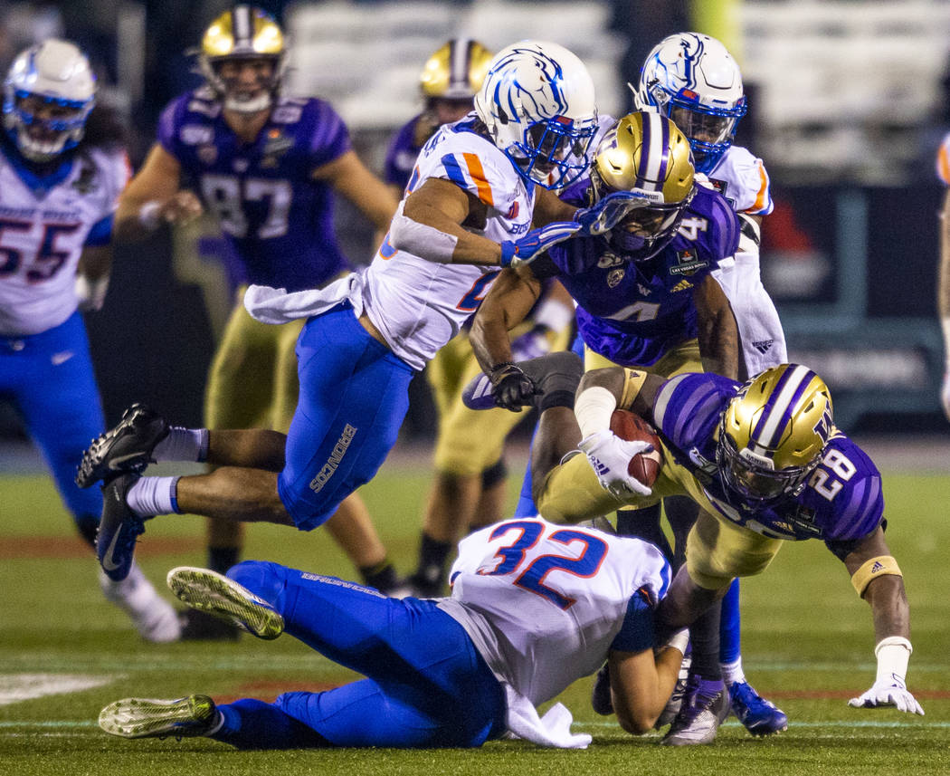 Washington Huskies running back Richard Newton (28, right) dives for more yards while tackled b ...