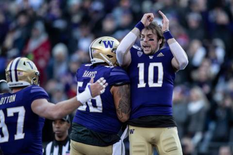 Washington quarterback Jacob Eason, right, celebrates scoring a touchdown with teammates tight ...