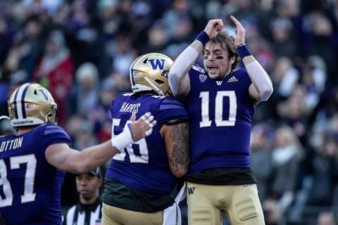 Washington quarterback Jacob Eason, right, celebrates scoring a touchdown with teammates tight ...