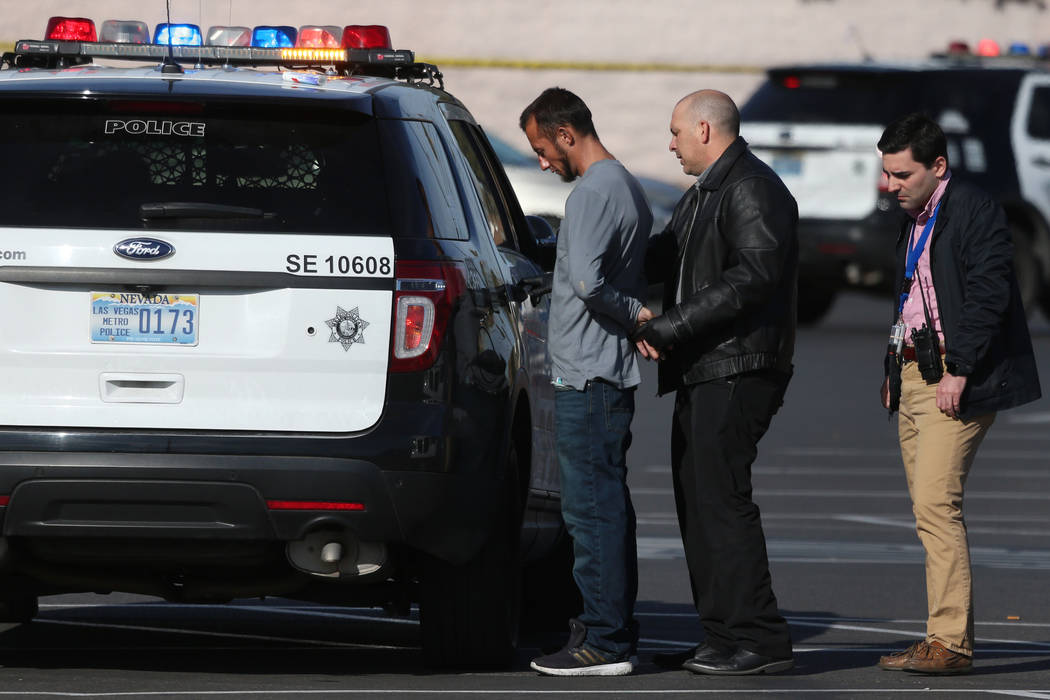 A person is detained at the scene of a shooting at the Tropicana Centre, 3000 block of E Tropic ...