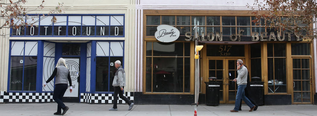 Pedestrians walk past the former Beauty Bar, right, and an unoccupied store, suite no. 110 at 5 ...