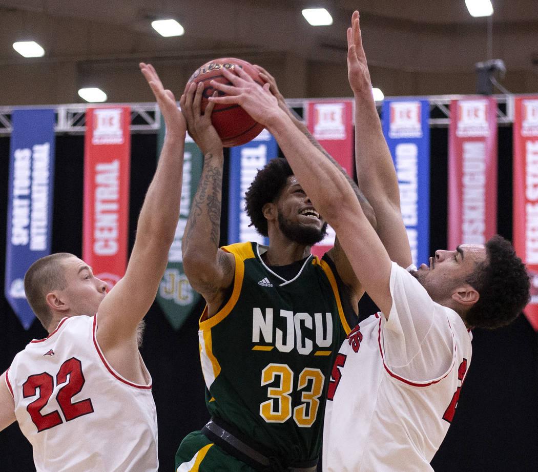 New Jersey City University's center Quadri Moore (33) shoots a point as University of Wisconsin ...