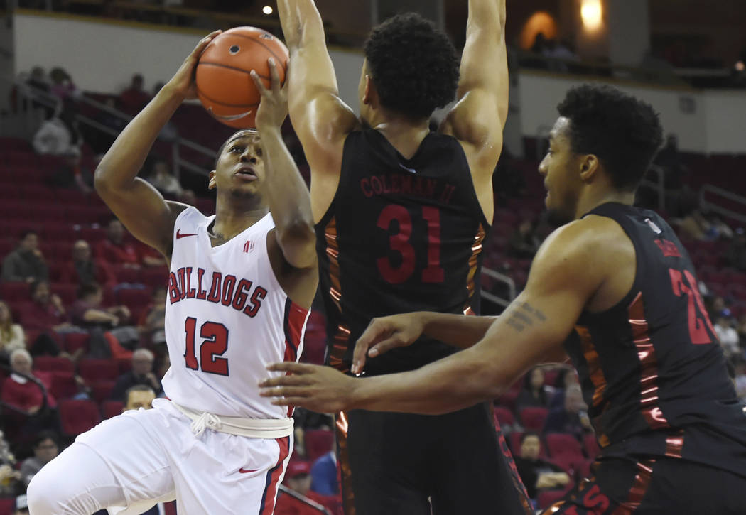 Fresno State's Mustafa Lawrence, left, goes up blocked by UNLV's Marvin Coleman, center, and Ni ...