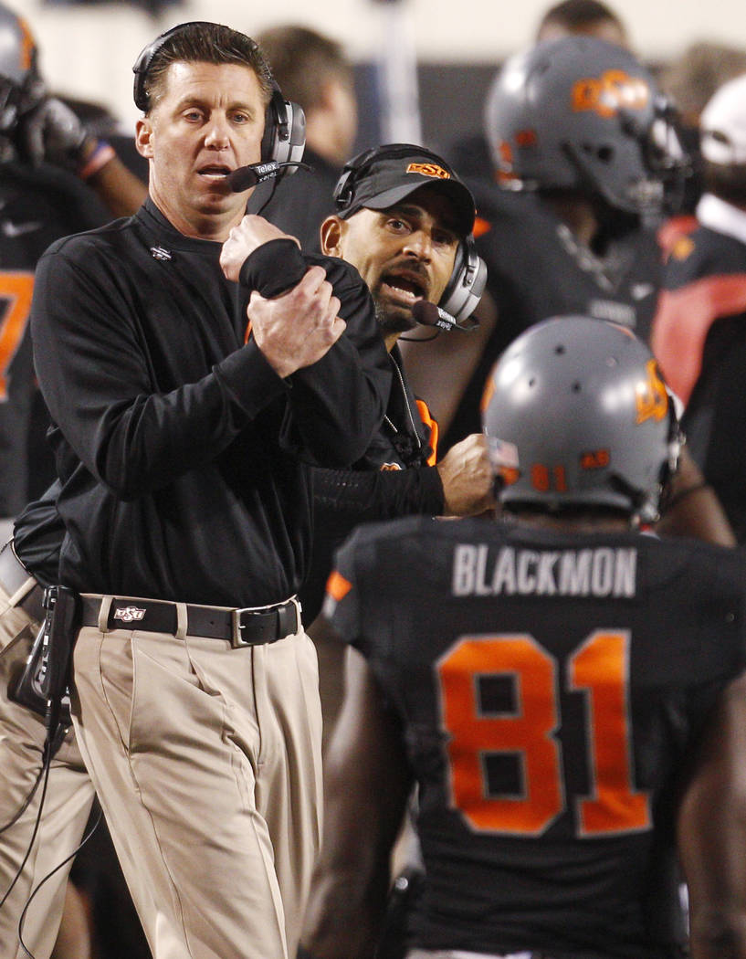 Oklahoma State head coach Mike Gundy, left, and wide receiver coach Kasey Dunn, center, shout t ...