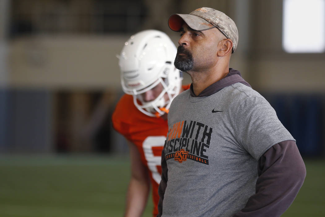 Oklahoma State's Kasey Dunn, associate head coach/receivers coach, watches during an NCAA colle ...