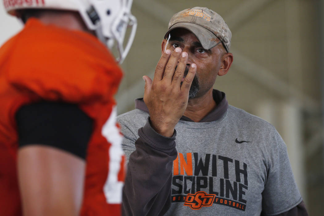 Oklahoma State's Kasey Dunn, associate head coach/receivers coach, talks to a player during an ...