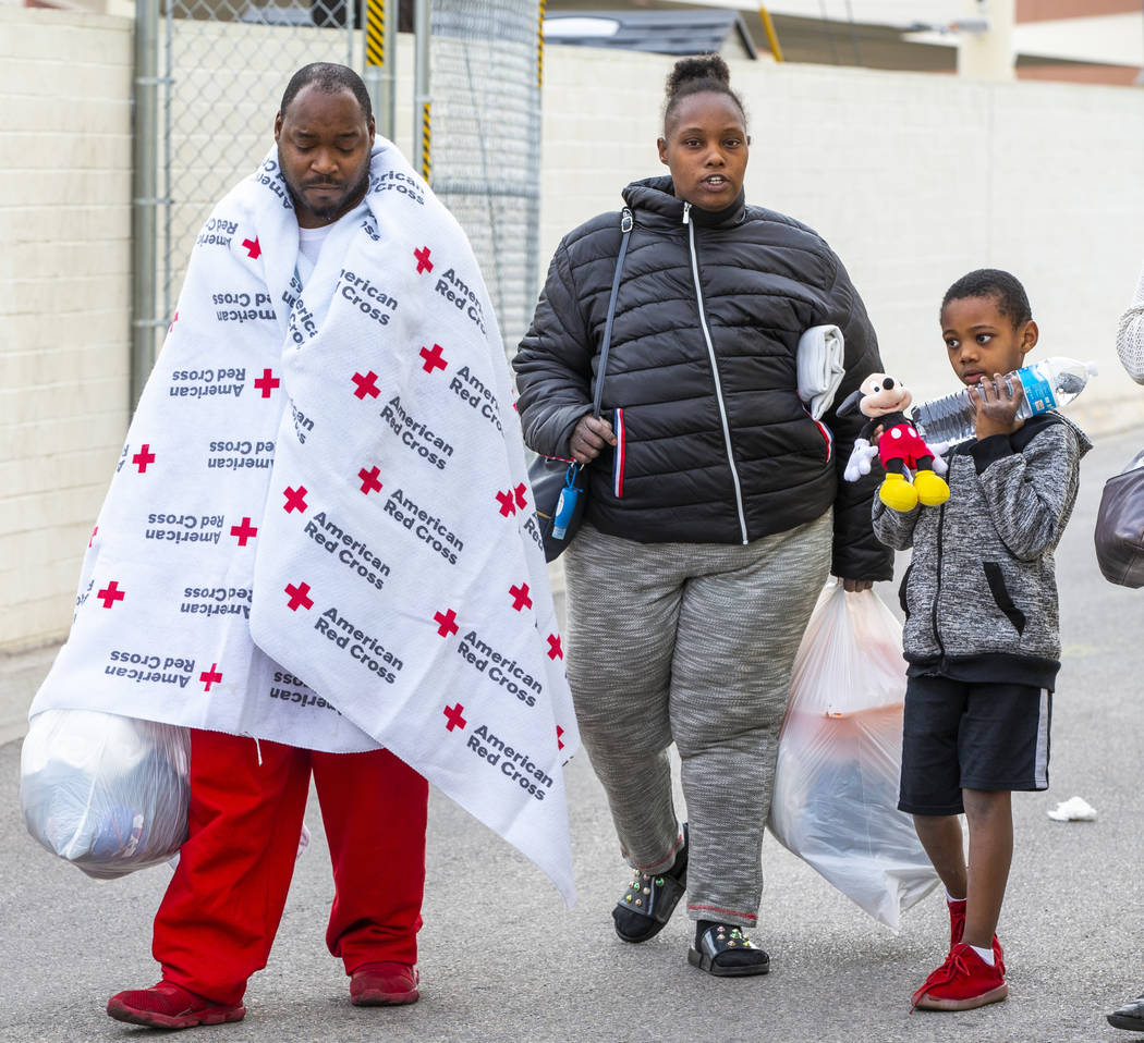 Alpine Motel Apartments residents Jimmy Lacy, left, Dayshena Thomas and Andru Roach, 7, depart ...