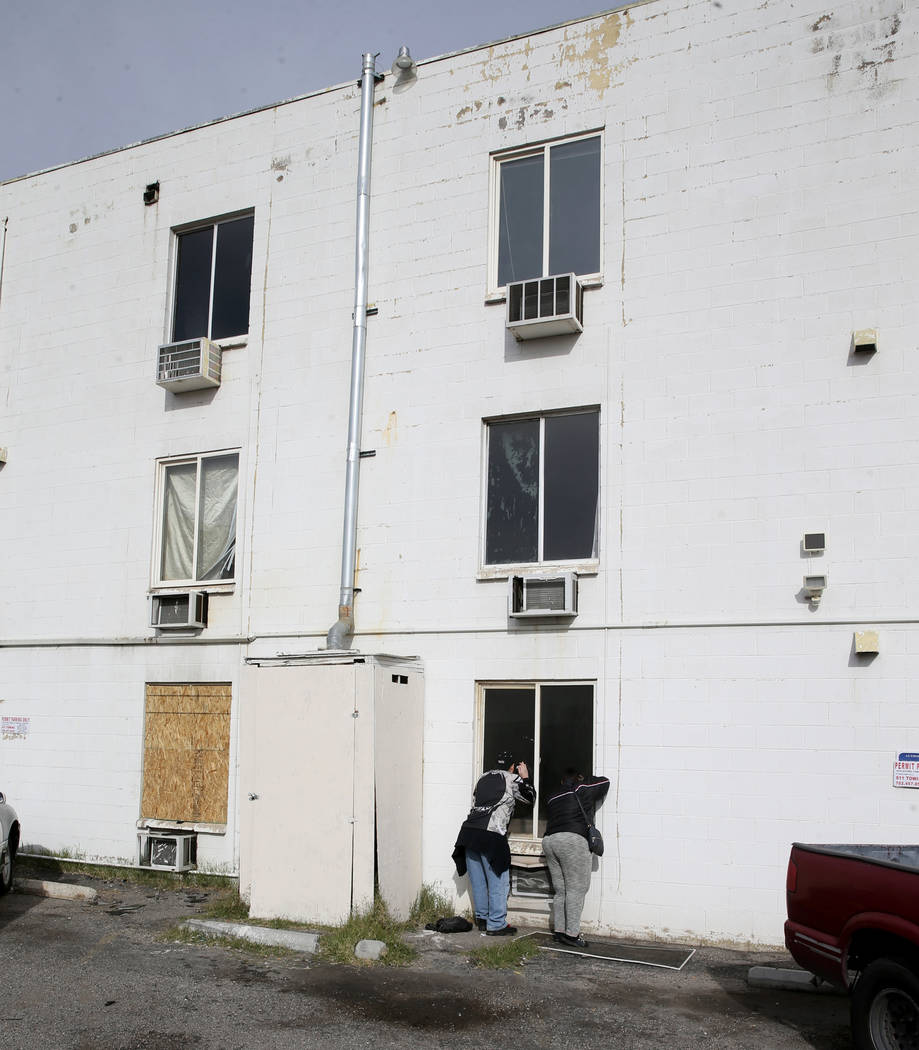 Residents gather at Alpine Motel Apartments after a fire left 6 dead and 13 injured at the down ...