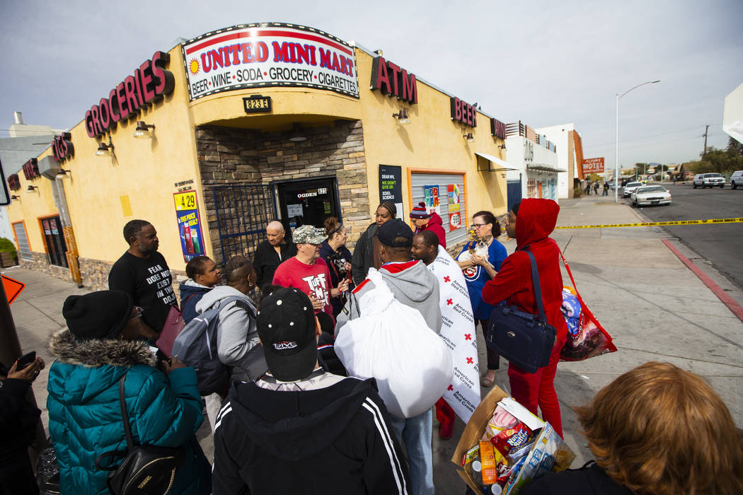 Displaced residents gather outside of the Alpine Apartment Motel, where an early morning fire l ...