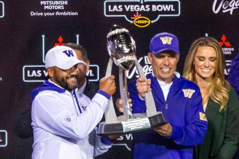 Washington Huskies head coach Chris Petersen, center, and incoming head coach Jimmy Lake, left, ...