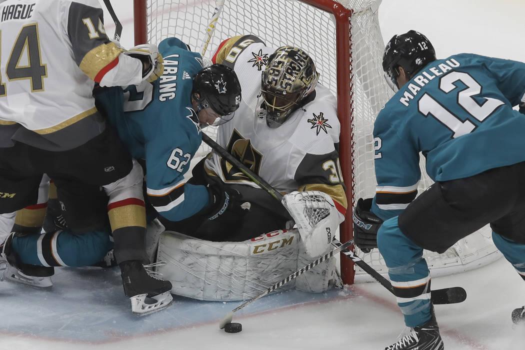 Vegas Golden Knights goaltender Malcolm Subban, center, defends the net as San Jose Sharks righ ...