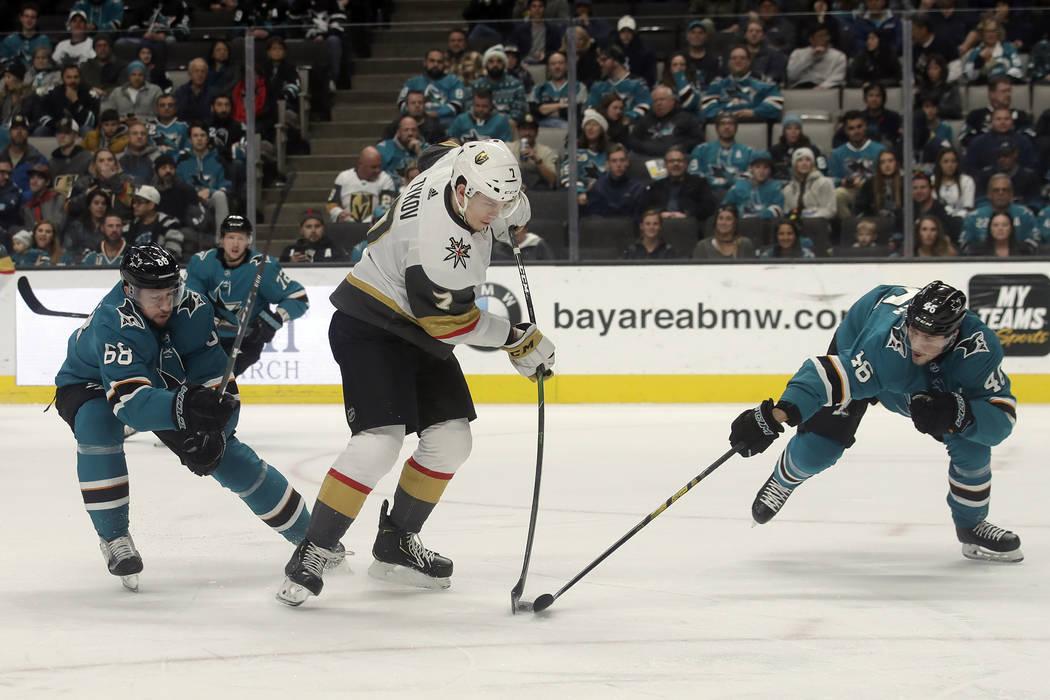 Vegas Golden Knights' Valentin Zykov, center, hits the puck between San Jose Sharks center Melk ...