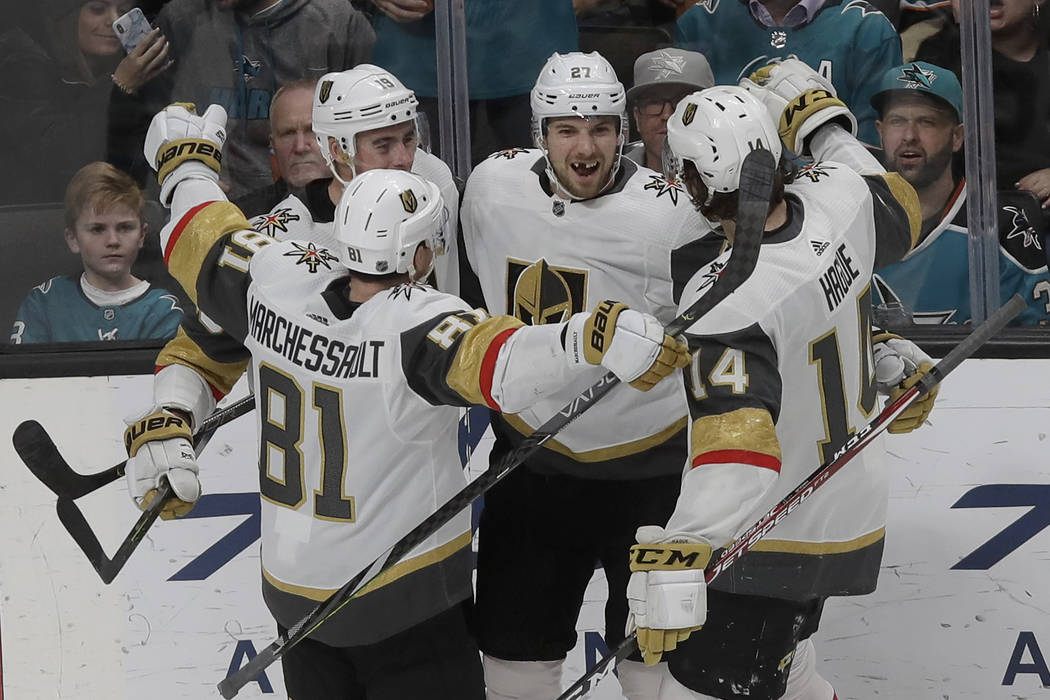 Vegas Golden Knights defenseman Shea Theodore, center, is congratulated by teammates after scor ...