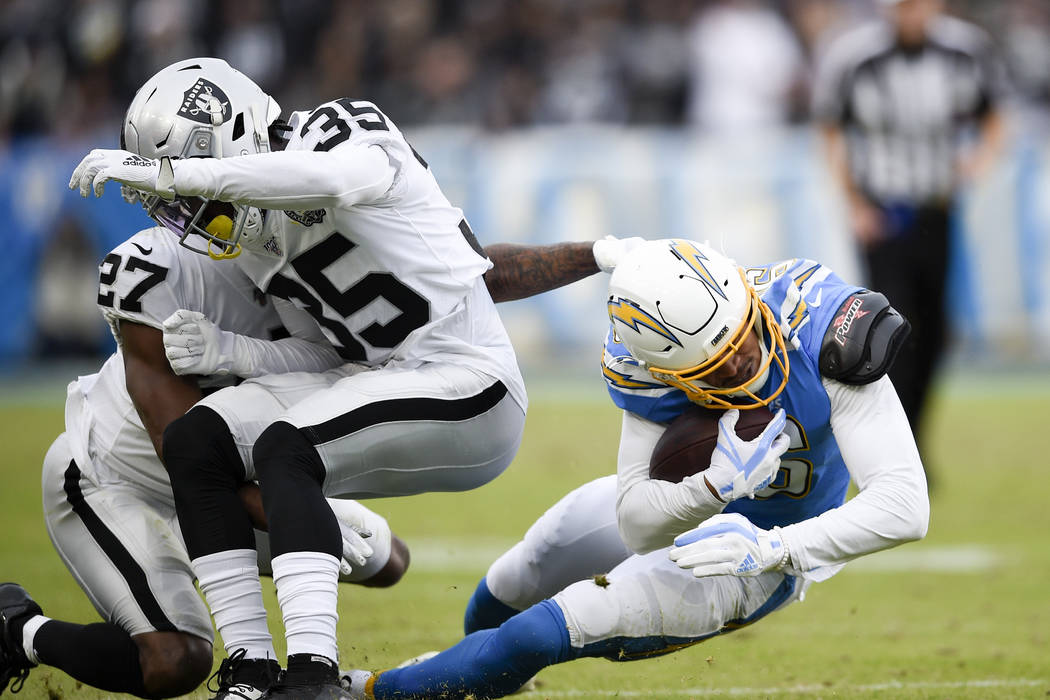 Oakland Raiders free safety Curtis Riley, middle, collides with teammate cornerback Trayvon Mul ...