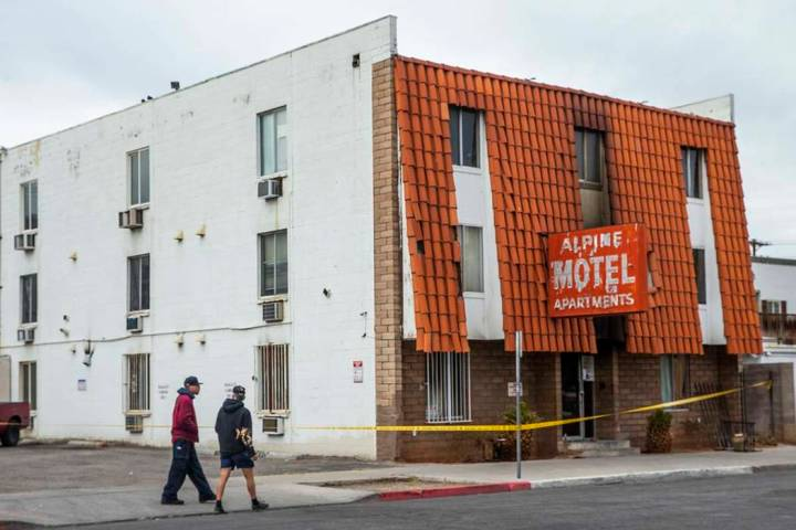 Pedestrians walk past the Alpine Apartment Motel with crime tape still in place on Sunday, Dec. ...