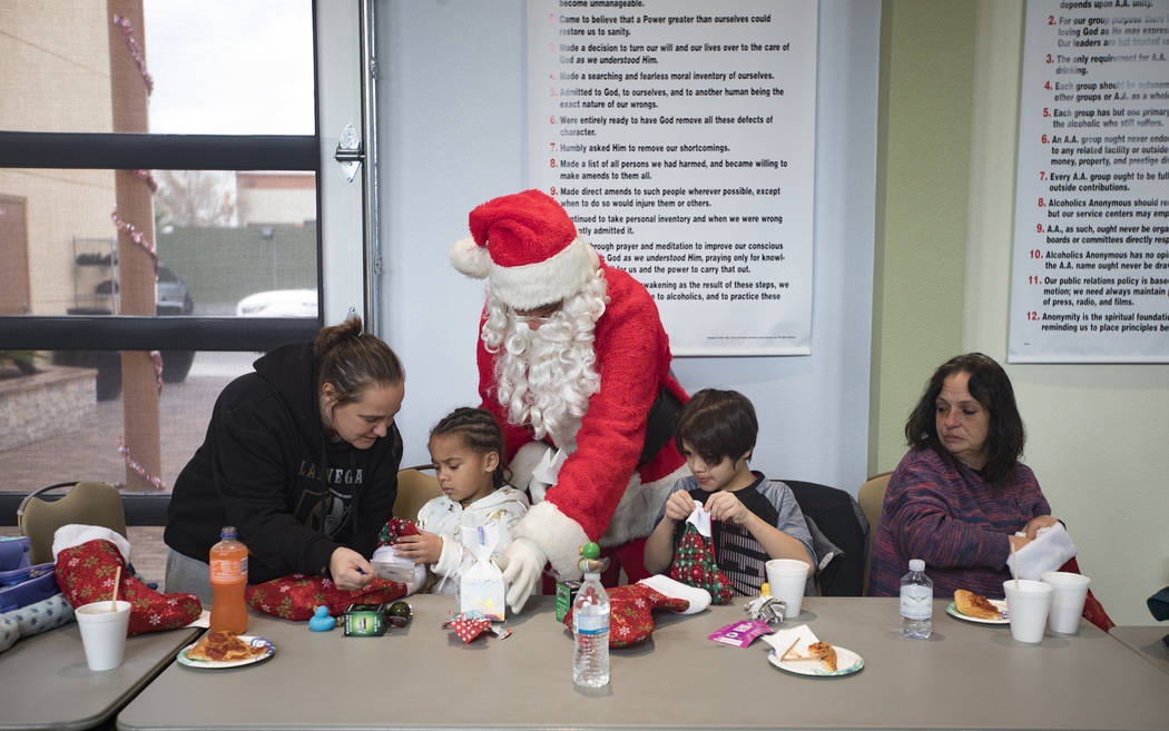 Santa Claus passes out gifts to the survivors of the Alpine Motel fire that killed six people a ...