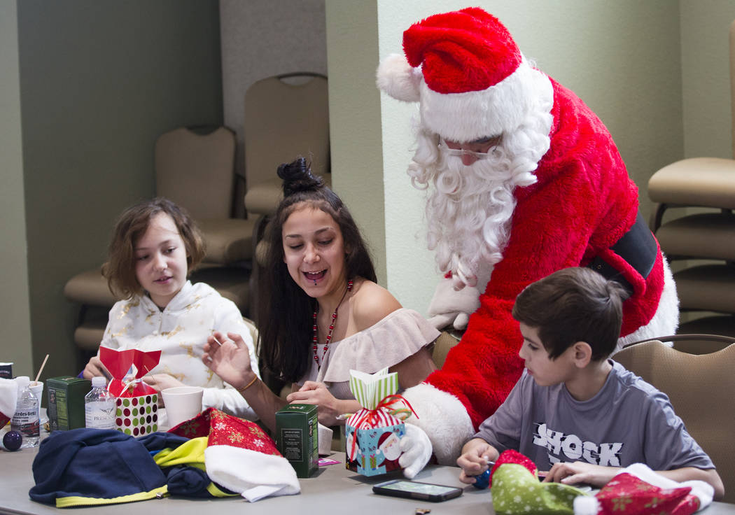 Santa Claus passes out gifts to survivors of the Alpine motel fire from left Brianna Aikens, 11 ...
