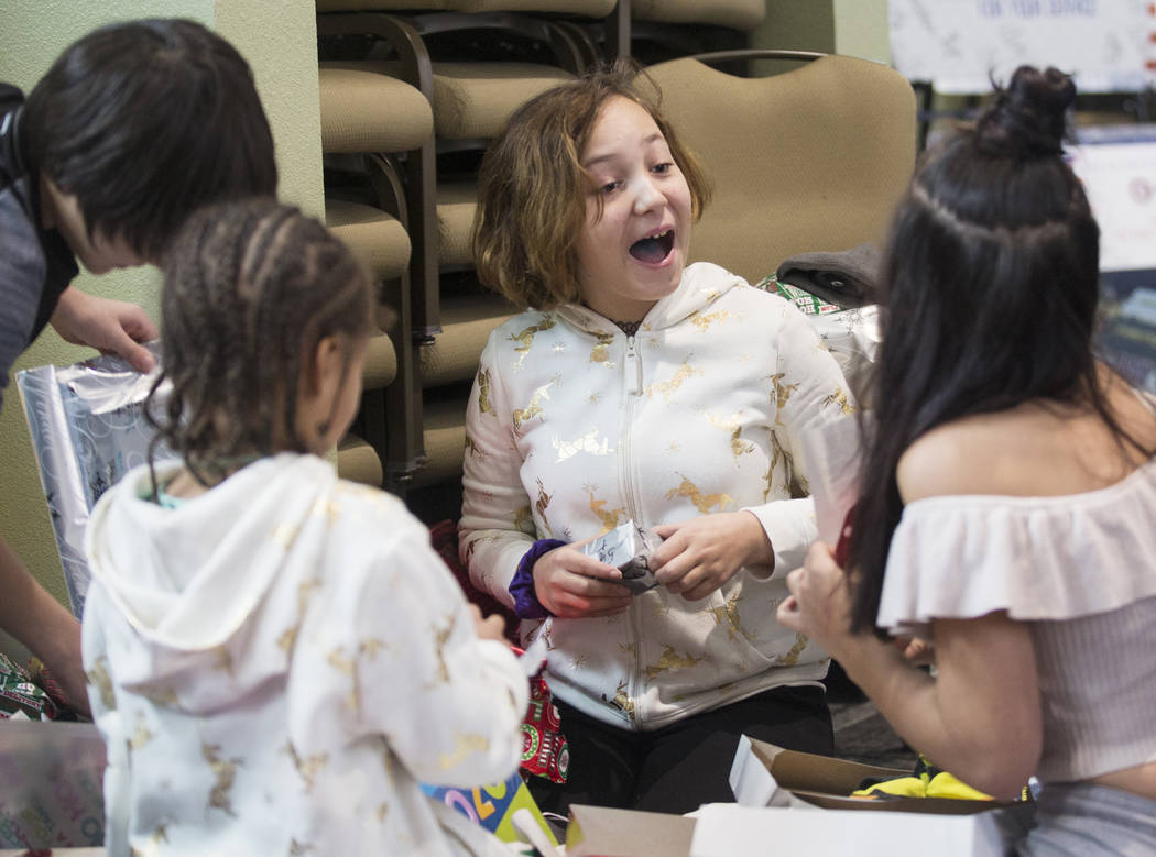 Brianna Aikens, 11, opens gifts with other survivors of the Alpine motel fire at SHARE Village ...