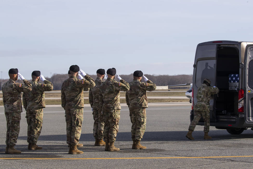 An Army carry team slaues a transfer case containing the remains of U.S. Army Sgt. 1st Class Mi ...