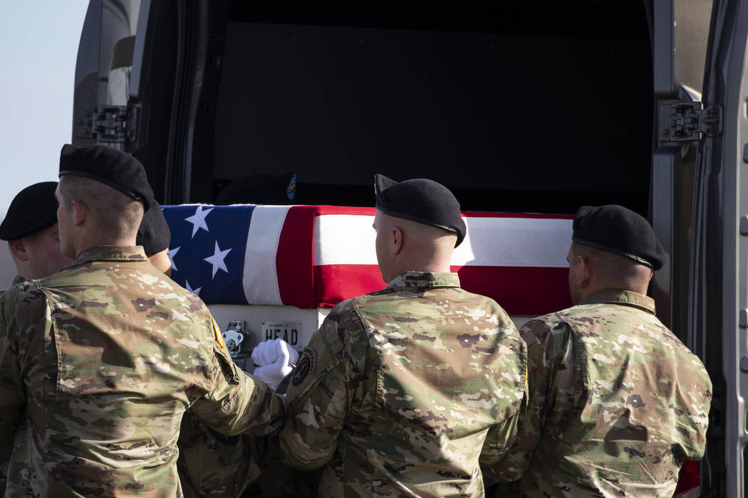 An Army carry team loads a transfer case containing the remains of U.S. Army Sgt. 1st Class Mic ...