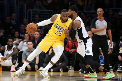 Los Angeles Lakers' LeBron James (23) is defended by Los Angeles Clippers' Paul George during t ...