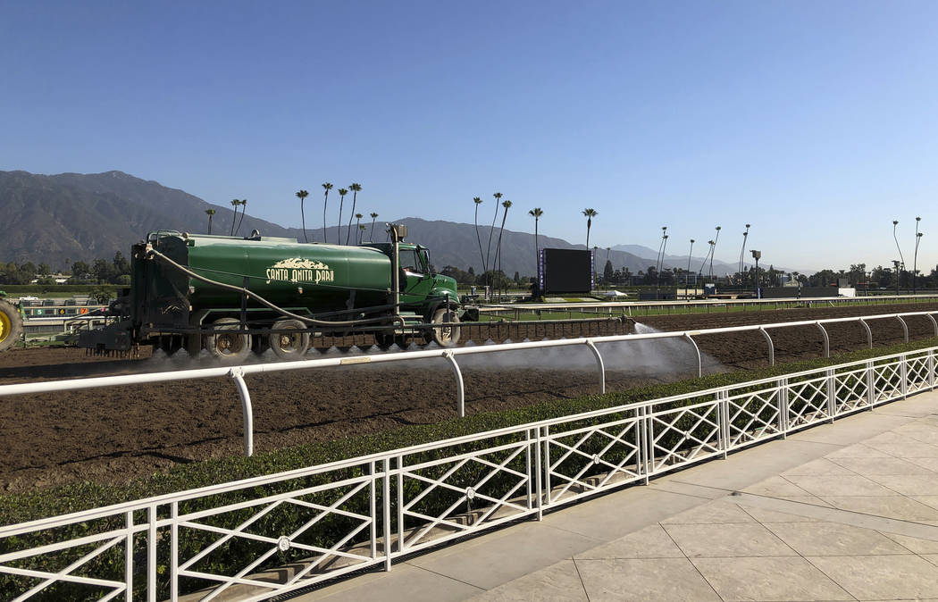 A truck waters the track at Santa Anita Park in Arcadia, Calif., Wednesday, Oct. 30, 3019. A tr ...