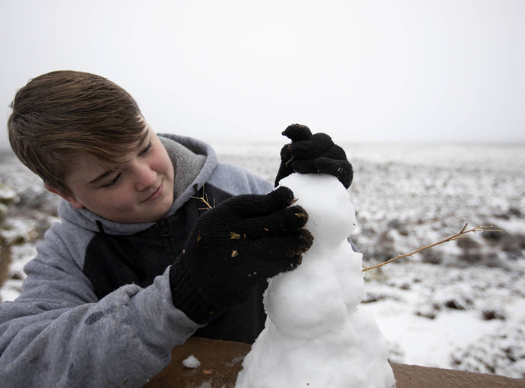 Jacob Luke, 14, of Las Vegas, makes a snowman at Red Rock Canyon Overlook on Thursday, Dec. 26, ...